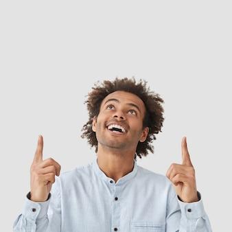 Il modello di uomo positivo guarda allegramente verso l'alto, ha un sorriso amichevole, mostra denti bianchi perfetti, indica con entrambe le dita anteriori sopra la testa
