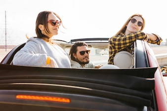 Positive man sitting in car near smiling women leaning out from auto