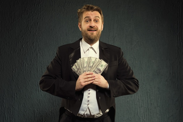 Positive man in a tailcoat hold money.