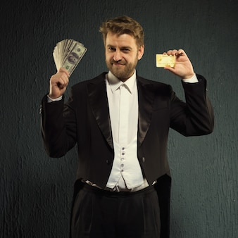 Positive man in a tailcoat offers a credit card and money.