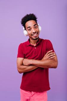 腕を組んで見ている大きな茶色の目を持つポジティブな男。ヘッドフォンでブルネットの陽気な男の子。