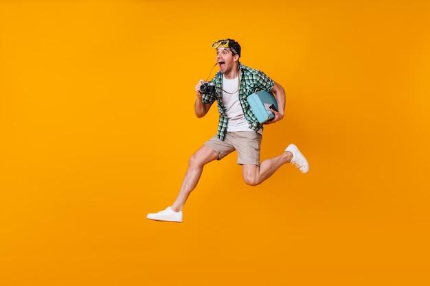 頭にダイビングマスクをかぶったポジティブな男性がレトロなカメラで写真を撮ります。オレンジ色のスペースでスーツケースとジャンプするショートパンツと緑のシャツの男。