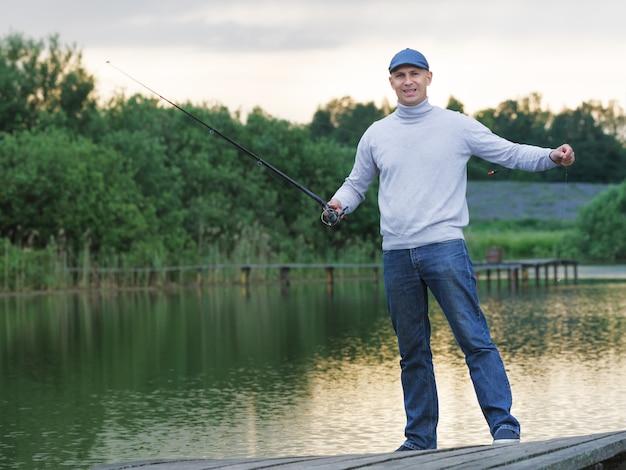 Позитивный человек с удочкой на озере