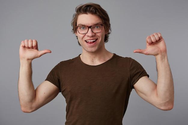 L'uomo positivo con gli occhiali indossa una maglietta bianca in piedi su uno sfondo grigio e indica se stesso con le dita, sembra allegro e in generale sorride e dice