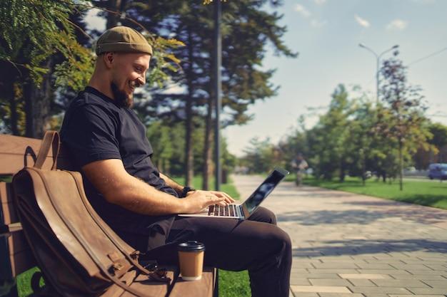 都市公園の距離の仕事でベンチに座っている間、外でリモートワークをしているラップトップを持つポジティブな男
