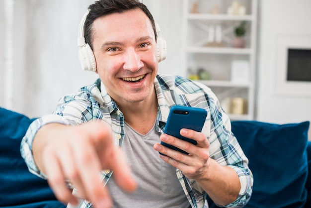 Positive man with smartphone listening music in headphones on sofa