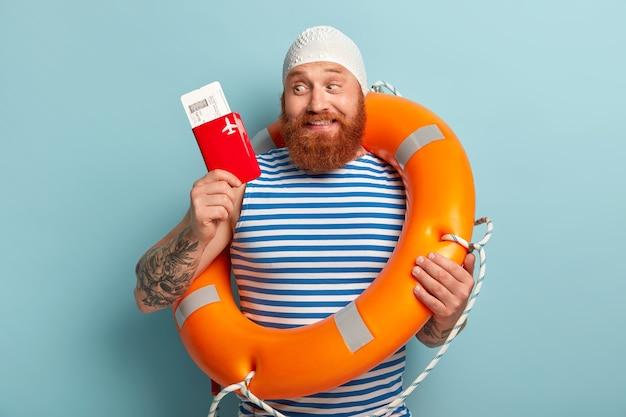 두꺼운 여우 수염을 가진 긍정적 인 남자, 여름 여행을 행복하게 생각하고 비행 준비가되어 여권과 티켓을 보유하고 있습니다.