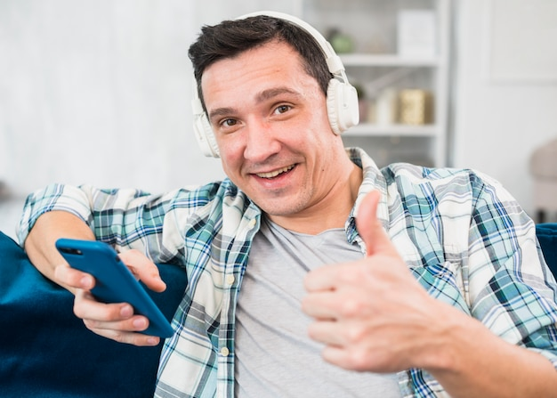 Positive man with thumb up listening music in headphones and browsing on smartphone on sofa