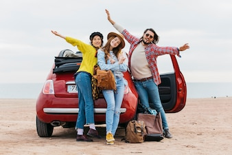 Positive man with upped hands near embracing women and car on sea beach