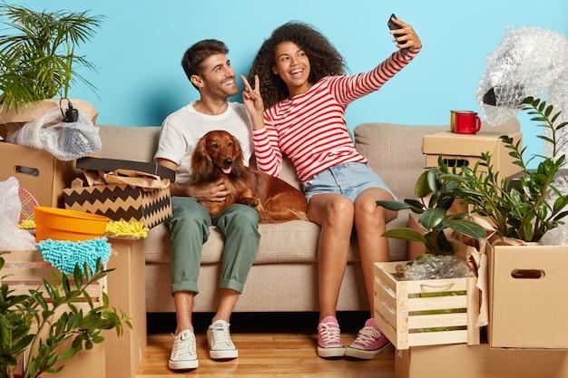 Coppia sposata positiva sul divano con il cane circondato da scatole di cartone