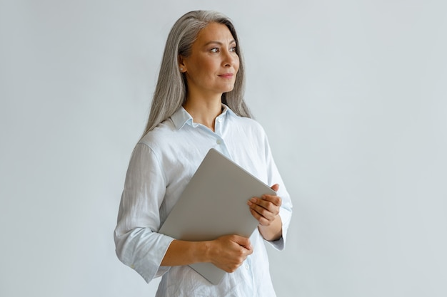 Positive mature asian businesswoman wearing white blouse holds contemporary laptop standing on light grey background in studio