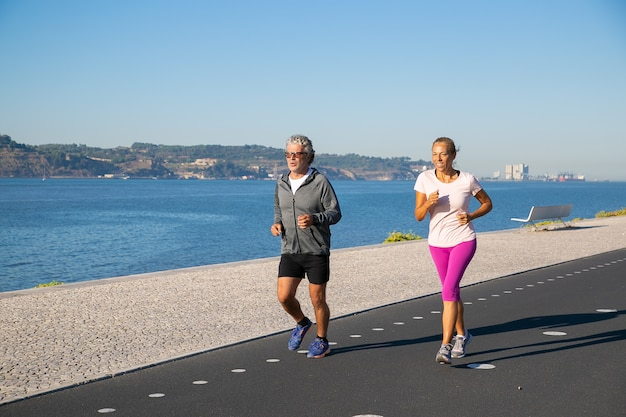 Positive mature couple keeping active lifestyle and jogging along river bank in morning. retired people activity concept