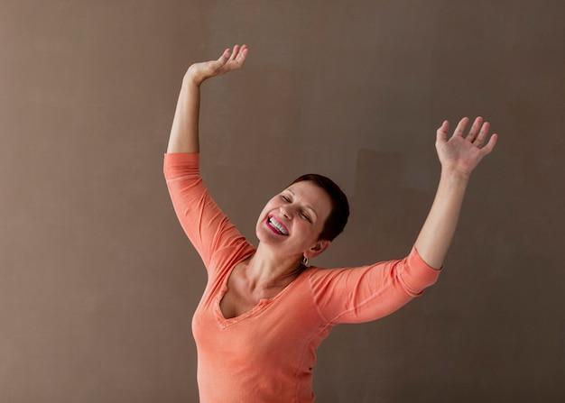 Positive mature lady raising hands