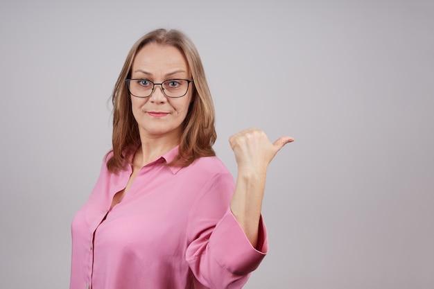 분홍색 블라우스를 입은 긍정적 인 성숙한 여인이 엄지 손가락을 옆으로 보여줍니다. 스튜디오 복사 공간이 회색 배경 위에 촬영.