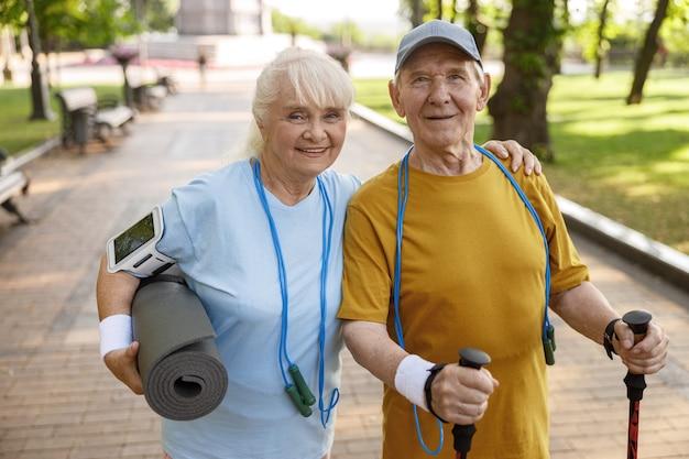 Позитивная зрелая женщина и мужчина со спортивным снаряжением позируют перед камерой в зеленом городском парке