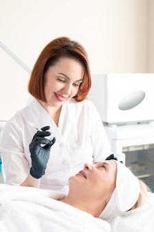 Позитивный медицинский косметолог держит шприц и разговаривает со зрелым клиентом, делая филлеры для лица во время процедуры омоложения кожи