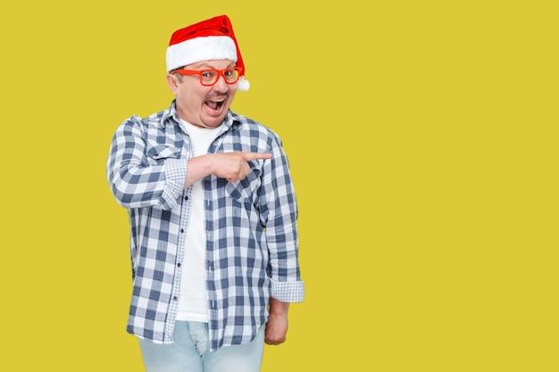 Позитивный мужчина средних лет в красной новогодней шапке санта-клауса и повседневном стиле, стоя, указывая пальцем на пустое пространство для копирования и с удивленным лицом, глядя в камеру. студия выстрел, изолированные на желтом фоне