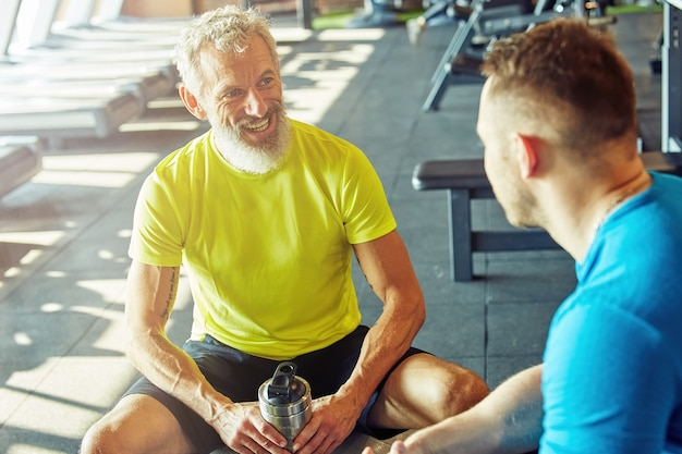 Positive middle aged man in sportswear holding bottle of water talking with his personal trainer or