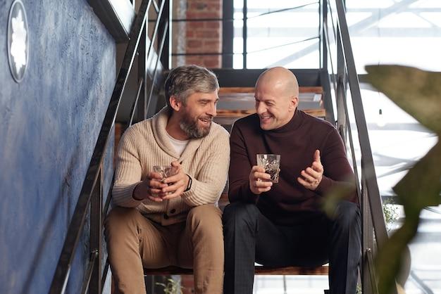 Позитивные мужчины среднего возраста в повседневной одежде сидят на лестнице и пьют алкоголь, весело проводя время вместе