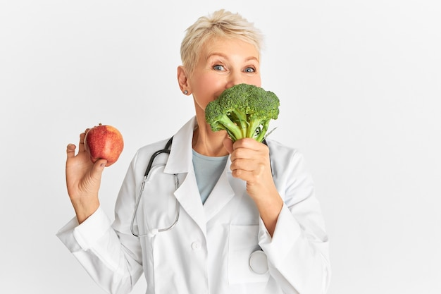Positive middle aged woman physician holding apple and broccoli, recommending plant based diet. funny female doctor suggesting eating vegetables which provide vital nutrients, low in fat and calories