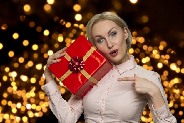 Positive middleaged woman is pointing at the gift box