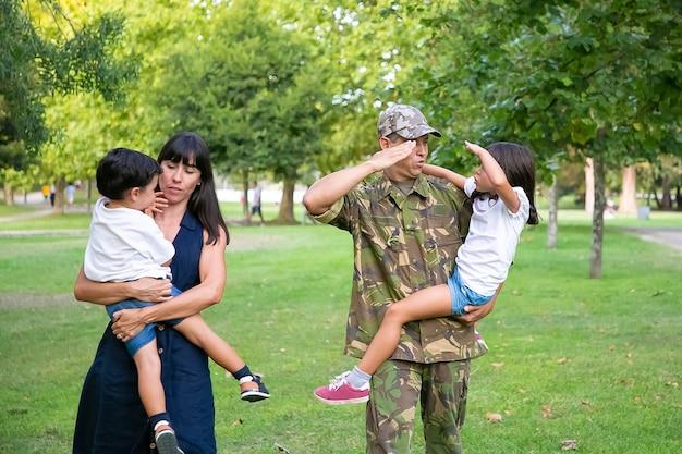Militare positivo che cammina nel parco con sua moglie e figli, insegnando alla figlia a fare il gesto di saluto dell'esercito. lunghezza intera, vista posteriore. ricongiungimento familiare o concetto di padre militare