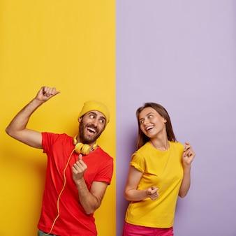 Coppia millenaria positiva in posa contro la doppia parete colorata