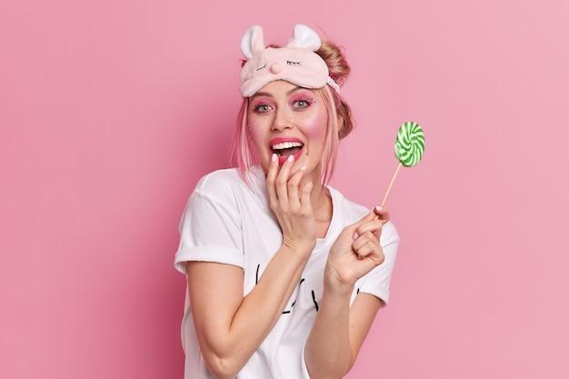 Позитивная миллениальная девушка счастливо улыбается, держит руку на открытом рту и держит вкусный сладкий леденец