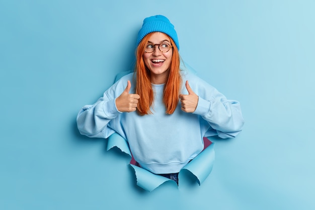 Positive millennial girl with natural ginger hair recommends sales keeps thumbs up and smiles gladfully gives approval wears blue hat and sweatshirt breaks through paper hole