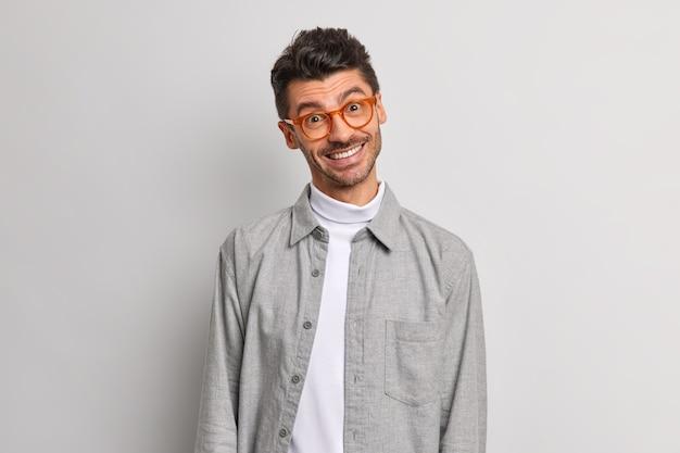 긍정적 인 밀레 니얼 세대의 남자는 고개를 기울이고 미소를 지으며 진지한 감정을 행복하게 표현합니다.