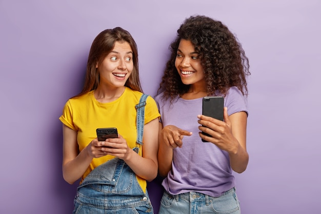 Positive millennial mixed race sisters pose with modern smartphone devices, addicted to technologies, chat online