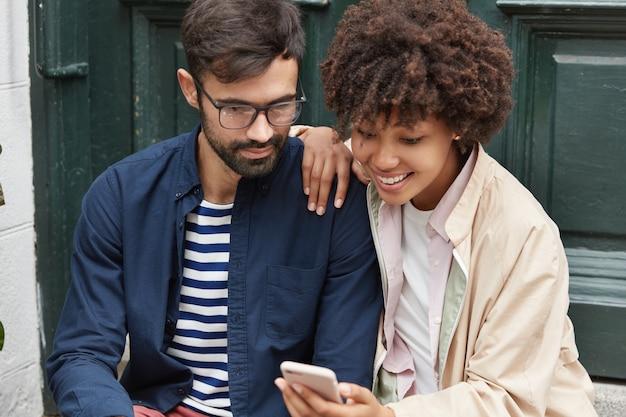 Coppia di razza mista positiva guarda contenuti video online divertenti sul cellulare, posa all'aperto