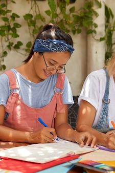 ポジティブな混血の女性は、ヘッドバンド、ピンクのサラファン、透明な眼鏡をかけ、クラスメートが近くに座っている日記にメモを書き、居心地の良いカフェのインテリアでポーズをとります。アサイン女性未来デザイナーがコースワークを準備