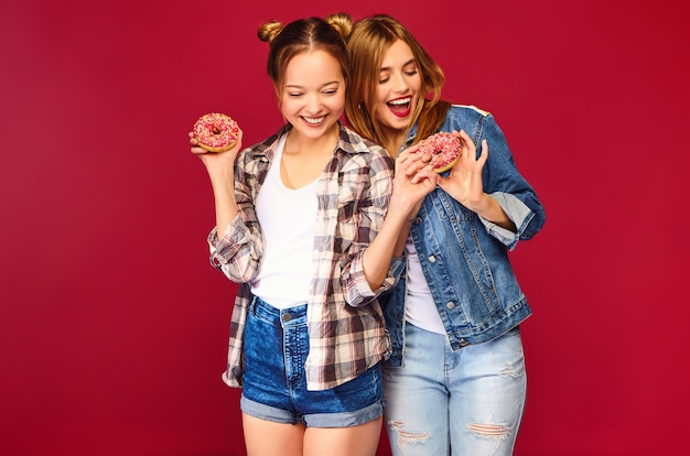 Positive models holding fresh pink donuts with powder ready to enjoy sweets