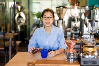 Positive modern barista knowing several methods how to brew coffee.