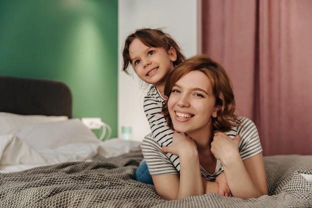 ポジティブなママと娘が楽しんで、抱き締めて、ベッドに横たわっています。