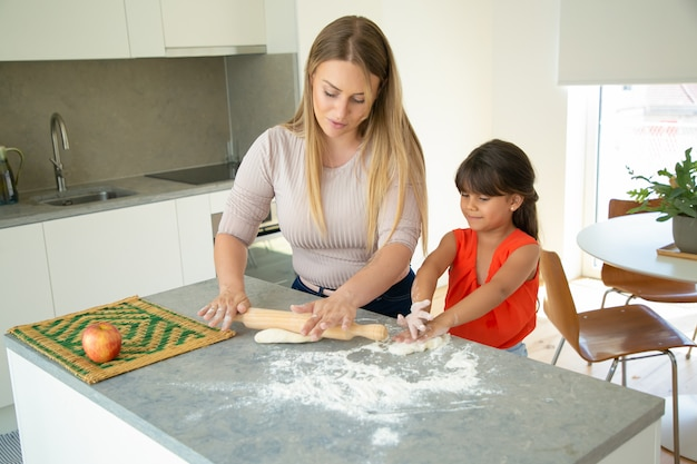 肯定的なママと娘が台所のテーブルで生地を圧延します。少女と母親が一緒にパンやケーキを焼きます。ミディアムショット。家族の料理のコンセプト