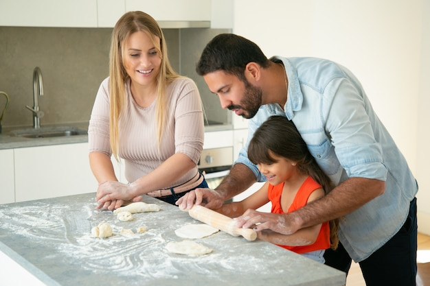Positive mom and dad teaching daughter to roll dough on kitchen table with flour messy. young couple and their girl baking buns or pies together. family cooking concept