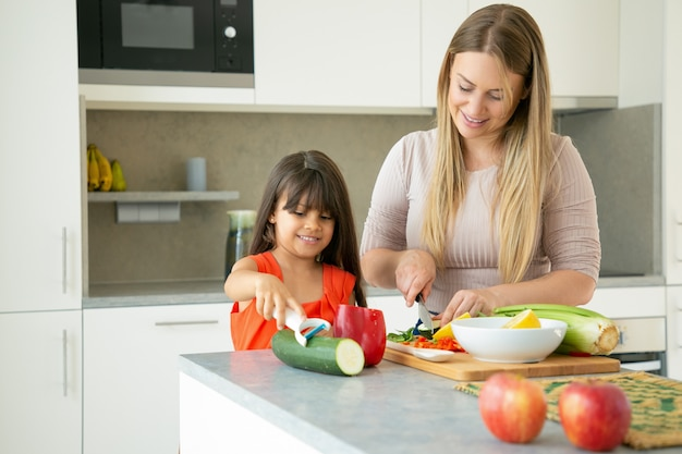 Positive mom and daughter cooking vegetables for dinner, smiling and talking. girl and her mother peeling and cutting vegs for salad on kitchen counter. family cooking concept