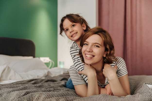Positive mom and daughter having fun, hugging and lying on bed.