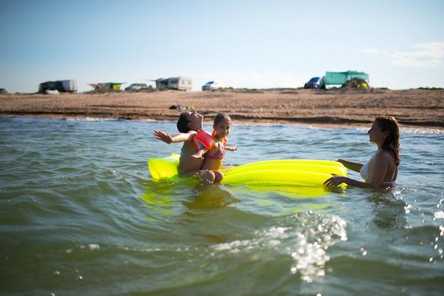 긍정적 인 엄마는 화창한 여름날 두 딸과 함께 바다에서 휴식을 취하고 있습니다. 바다와 여름 휴가에서 여름 휴가의 개념