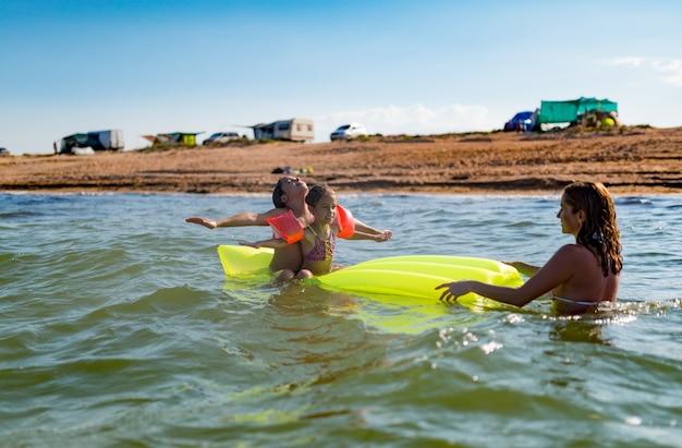 긍정적 인 엄마는 화창한 여름 날에 두 어린 딸과 함께 바다에서 휴식을 취하고 있습니다.