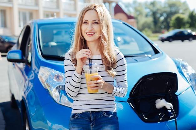 긍정적 인 분위기. 오렌지 주스를 들고 웃고 자동차 보닛에 기대어 기쁘게 행복 좋은 여자