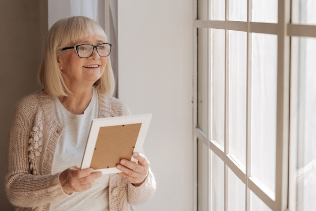 Positive mood. delighted nice aged woman looking into the window and smiling while holding a photograph
