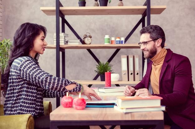 긍정적 인 분위기. 테이블에 앉아있는 동안 서로 웃고 기쁘게 좋은 사람들