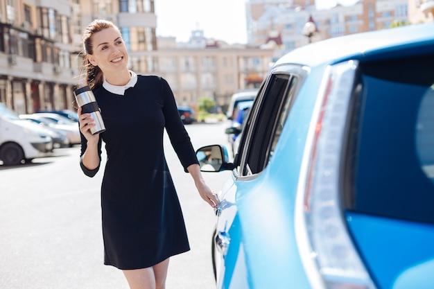 긍정적 인 분위기. 즐거운 매력적인 똑똑한 사업가 그녀의 차를 열고 그녀의 손에 열 컵을 가지고 웃고