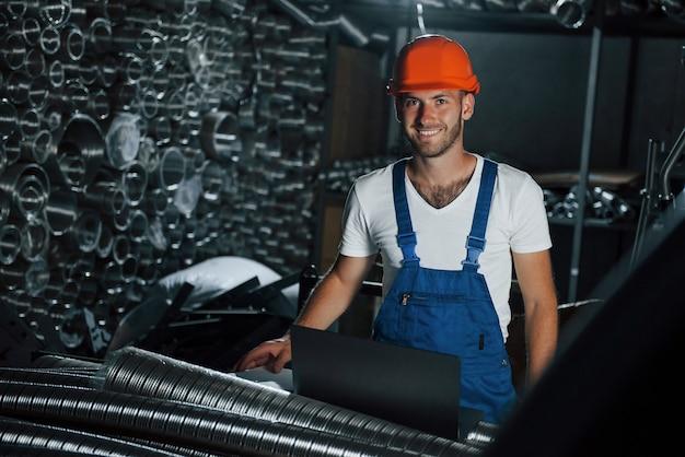 Положительный настрой. мужчина в военной форме работает на производстве. современные промышленные технологии.