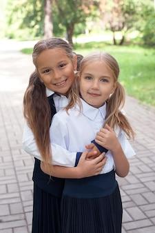 긍정적인 분위기. 공원에서 산책 하는 배낭과 함께 아름 다운 십 대 소녀입니다. 학교로 돌아가다. 배낭과 십 대 아이입니다. 우정의 개념입니다. 최고의 학교 친구. 즐겁게 학교에 갑니다. 배낭을 든 여학생들