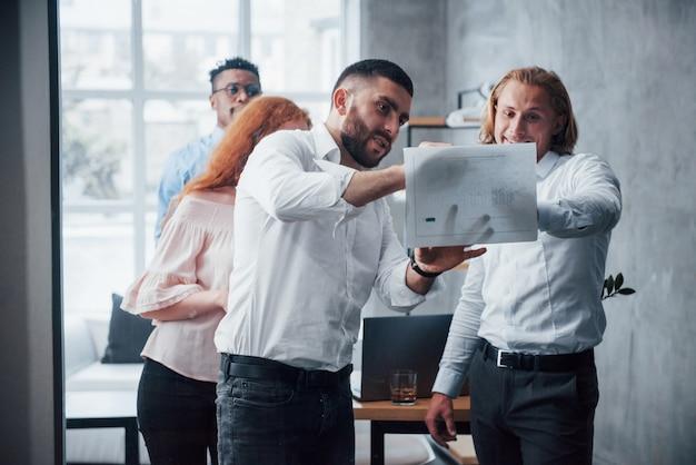 Позитивное настроение молодая многорасовая команда в официальной одежде в офисе, глядя на прайс-лист