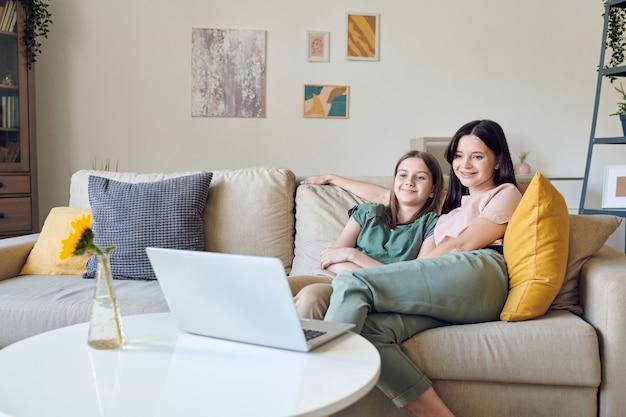 Позитивная мать и ее дочь-подросток сидят на диване и смотрят фильм на ноутбуке во время карантина